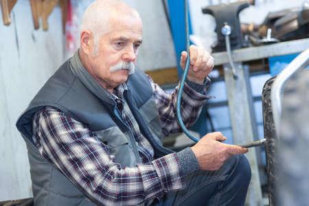senior mechanic works on vehicle
