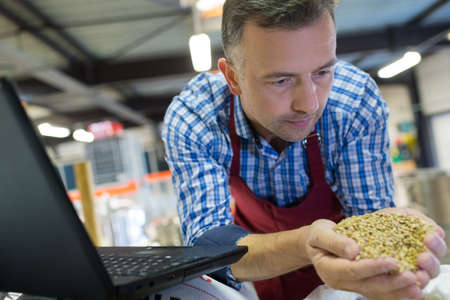 Man holding handful of grains next to laptop