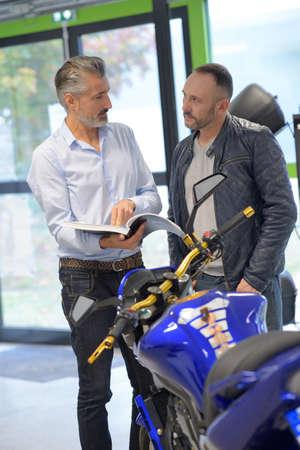 Biker with salesman in shop Stock Photo