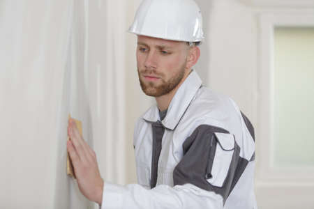 plasterer: young man sanding the wall