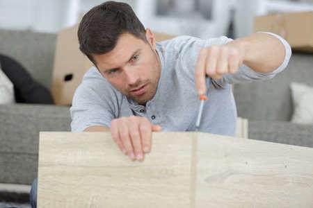 man in shirt assemble furniture