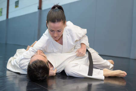 Woman on floor with opponent in karate hold