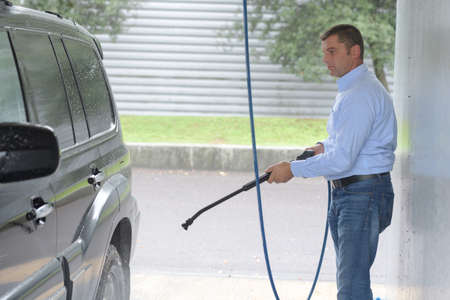 mpv: Man cleaning mpv with pressure washer