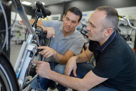 mechanic repairing battery powered bicycle in his workshop Foto de archivo
