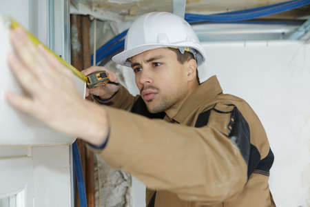 retractable: young man preparing to install cassette roller blinds on windows