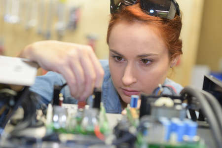 Woman looking closely at electronics board