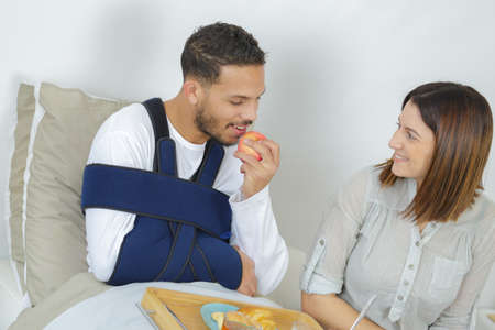 Injured man eating apple with left hand Stock Photo