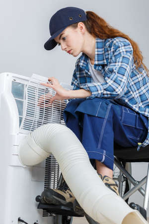 young beautiful woman opening air conditioner