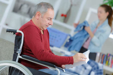 Man in wheelchair reading book, woman ironing in background Stock Photo