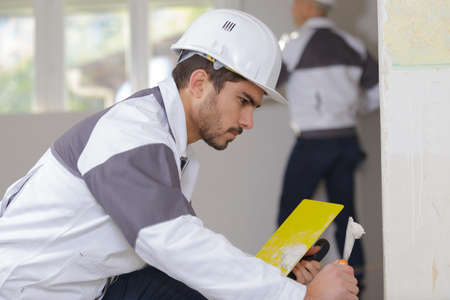 young apprentice plasterer working on indoor wall Stock Photo