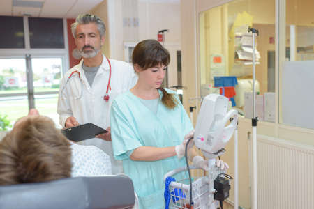 doctor and nurse interacting with patient in hospital room Stock Photo