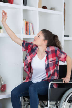 invalidity: Adolescent in wheelchair reaching up to shelf Stock Photo