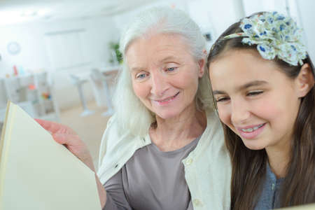 the grand daughter: grandmother and grand-daughter reading a book Stock Photo