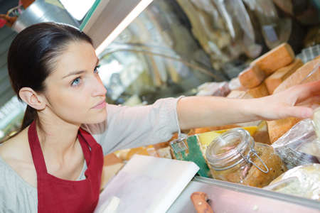 young female customer selling cheese for dessert in delicatessen store