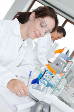 Smiling laboratory technician making notes