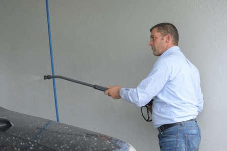 rinse spray hose: Man using power washer