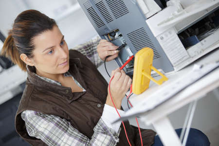 Technician using multimeter on appliance Stock Photo