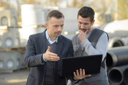 communication industry: male engineer using digital tablet outside industry