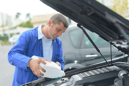diluted: Man refilling vehicle with screen wash