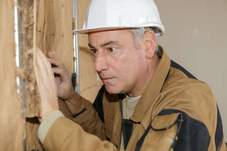 foremaster: plasterer worker at a indoors wall insulation works