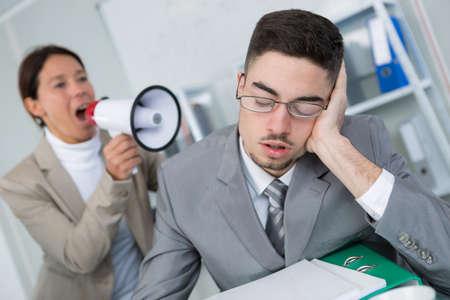 stressing: Woman shouting through loudhailer at sleepy office worker