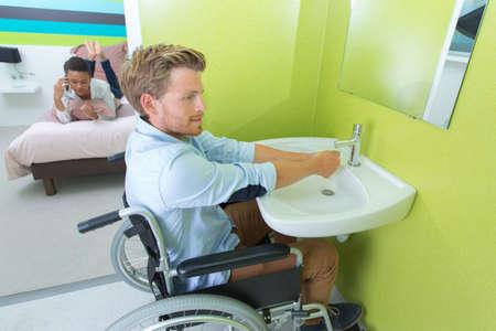 ensuite: Handicapped man using hotel facilities
