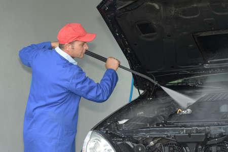 Man power washing vehicle engine bay
