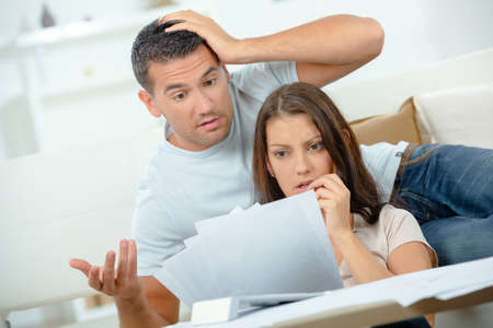 perturbed: Young couple looking in shock at bills