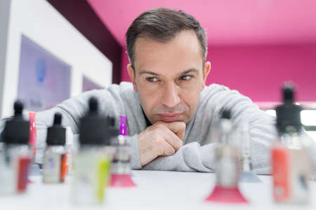 propylene: man leaning on counter contemplating bottles of electronic cigarette favours Stock Photo