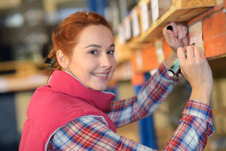 labelling: Woman labelling shelf under pallet in warehouse Stock Photo