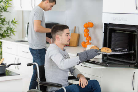 Disabled man taking food from oven