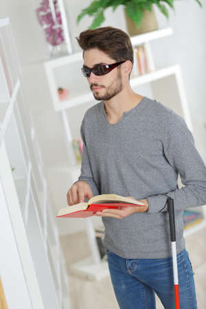 Man with sight impairment reading braille book Stock Photo
