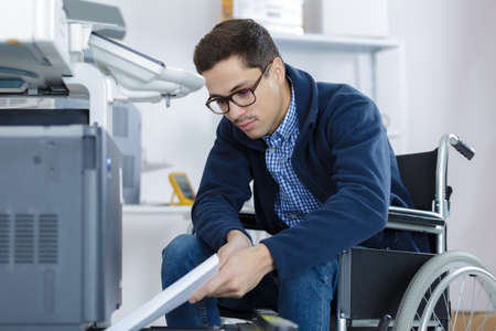 Man in wheelchair refilling photocopier paper tray