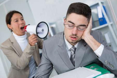 Woman using loudhailer to wake businessman Stock Photo