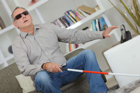Blind and deaf man using stick at home