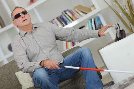 Homme aveugle et sourd avec un bâton à la maison Banque d'images