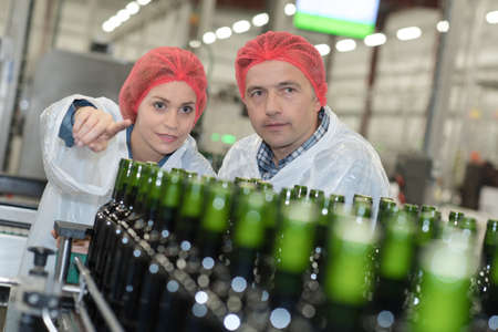 brewery: Factory workers looking at bottling plant Stock Photo