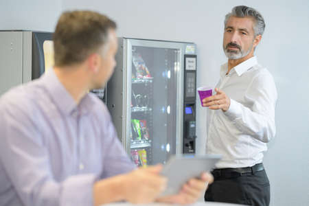 Businessman offering coffee from vending machine