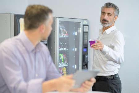 Zakenman die koffie van automaat aanbiedt Stockfoto