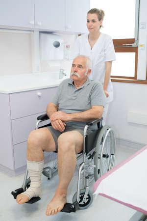 ulcer: Nurse pushing senior man in wheelchair Stock Photo