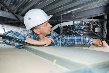 confined: Electrician installing cables into confined space