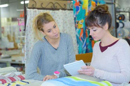 Women with list choosing fabric