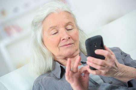 Elderly woman using a smartphone Stock Photo