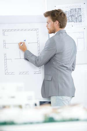 Architect drawing floorplan on easel