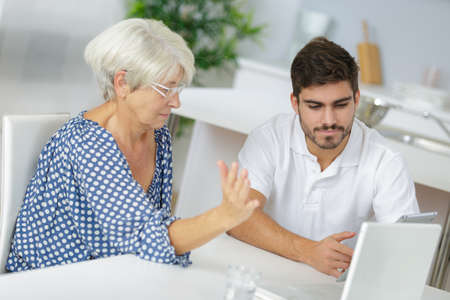 Young man and senior lady looking at tablet Stock Photo