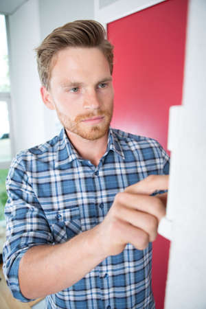 Young man entering code on indoor panel Stock Photo