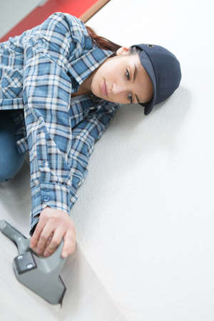 underlay: Woman knocking underlay against wall with tool