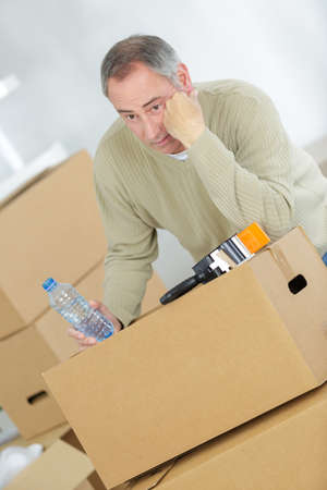 Miserable man with his belongings in cardboard boxes