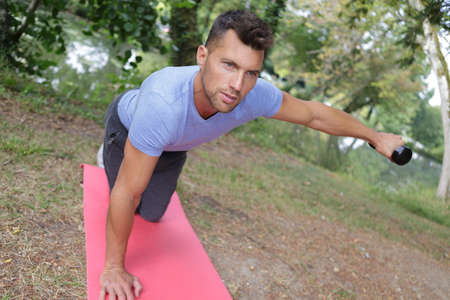 Man exercising with weights on a mat outdoors