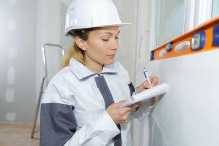 female builder checking work with spirit level Stock Photo